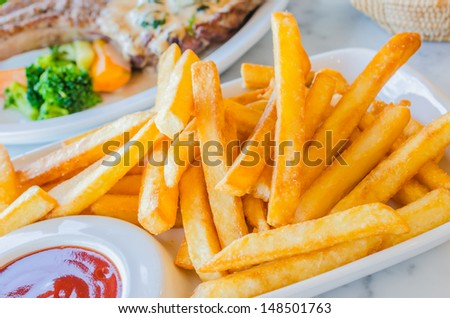 Fried Potato in white dish with tamato sauce - stock photo