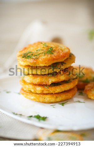 fried potato pancakes with dill on white plate - stock photo