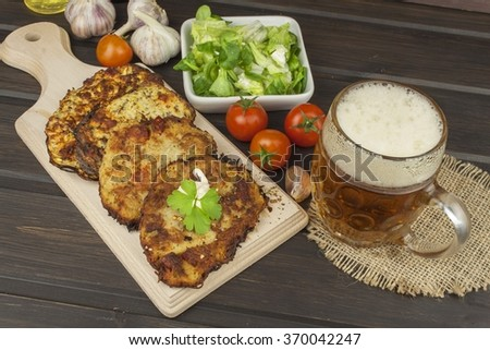 Fried potato pancakes with garlic. Traditional Czech food. Preparing homemade food. Potato pancakes and beer glasses.  - stock photo