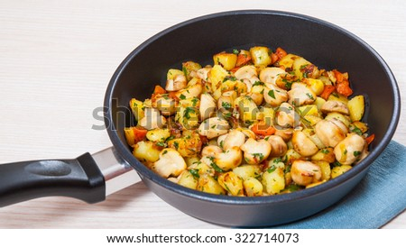 Fried potato with mushrooms in a frying pan - stock photo