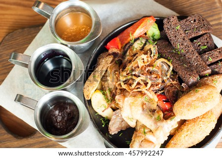 Fried potatoes chicken wings cutlets bread and different tasty sauces - stock photo