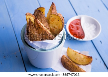 Fried potatoes on a cup and hot chili sauce on rustic blue wooden background - stock photo