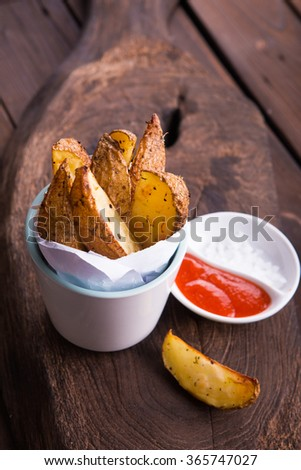 Fried potatoes on a cup and hot chili sauce on rustic brown wooden background - stock photo