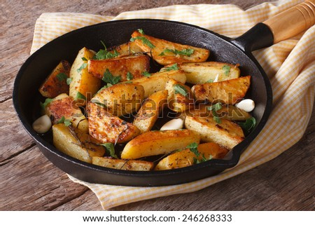 Fried potatoes on the iron frying pan close-up on the table. horizontal  - stock photo