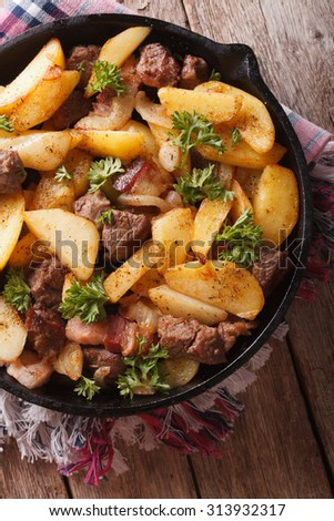 fried potatoes with meat and bacon served in a pan close-up. vertical view from above - stock photo