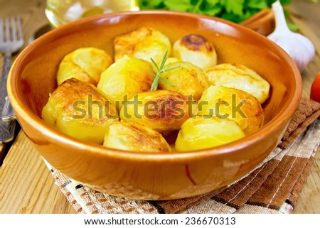 Fried potatoes with rosemary in a ceramic pan on a napkin, garlic, parsley, vegetable oil, fork on a wooden boards background - stock photo
