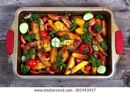 Fried potatoes with sausages, green parsley, fresh tomatoes and cucumbers. Greasy pan on old wooden table. - stock photo