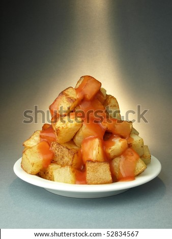 Fried potatoes with spicy sauce - stock photo