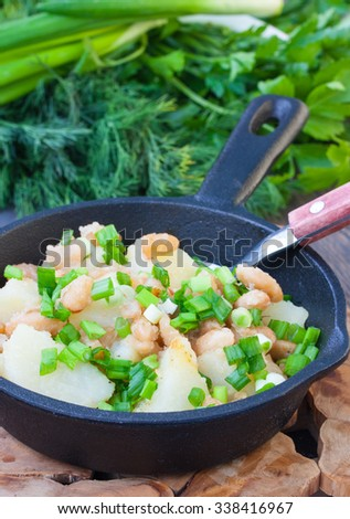 Fried potatoes with white beans with fresh chives in a cast iron skillet batch, selective focus - stock photo