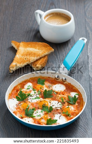 fried quail eggs in tomato sauce with toasts and coffee in a frying pan, vertical - stock photo
