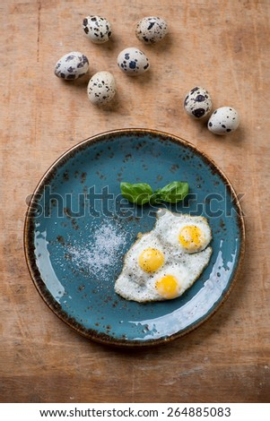Fried quail eggs on a turquoise plate, view from above - stock photo
