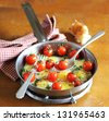 Fried quail eggs with cherry tomatoes, mozzarella cheese and chopped fresh curly parsley in a frying pan for breakfast - stock photo