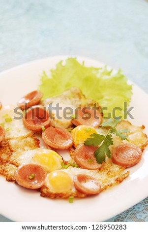 fried quail eggs with sausage and greens - stock photo