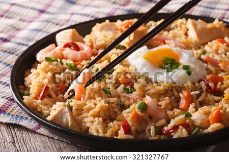 Fried rice nasi goreng with chicken, shrimp and vegetables close-up horizontal - stock photo