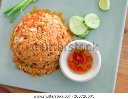 Fried rice tom yam with vegetables on wooden table, Thai food style, Sensitive focus point - stock photo