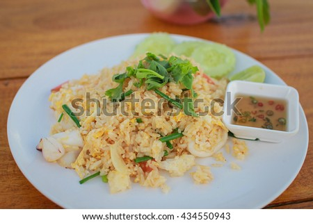 Fried rice with seafood,Asian fried rice nasi goreng with chicken, prawns, and fish baso  - stock photo