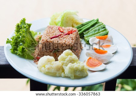 Fried rice with shrimp paste, salted egg and vegetables. - stock photo