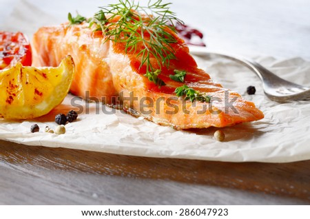 Fried Salmon fillet with lemon tomato and spices rustic serving - stock photo