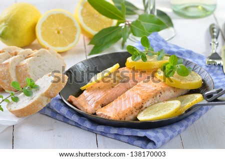 Fried salmon fillets with lemon slices - stock photo