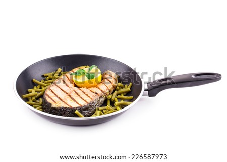 Fried salmon steak on pan as haute cuisine. Isolated on a white background. - stock photo