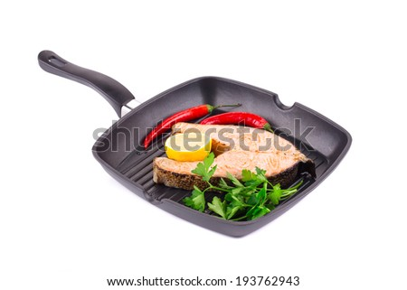 Fried salmon steak on pan. Isolated on a white background. - stock photo
