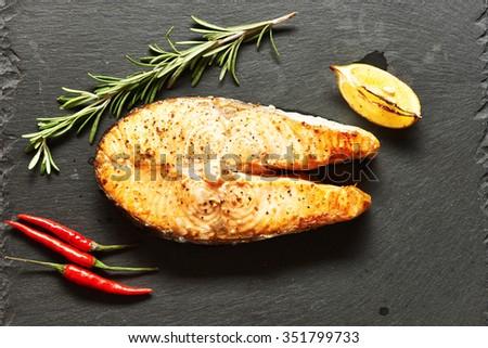 Fried salmon steak on slate background   - stock photo