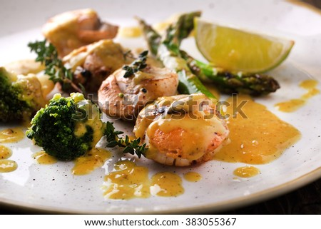 Fried scallops in a sauce with asparagus and broccoli on a plate - stock photo