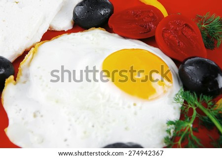 fried scrambled eggs eye with white goat feta cheese on red plate isolated over white background with black olives and vegetables - stock photo