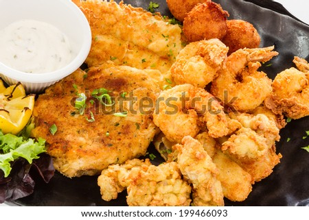 Fried seafood platter with fish, shrimp, oysters, hush puppies, and a crab cake. - stock photo