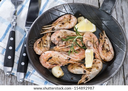 Fried Shrimps with garlich and herbs in a skillet - stock photo