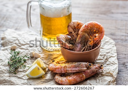 Fried shrimps with glass of beer - stock photo