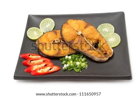 Fried Spanish mackerel display on dish on white background - stock photo