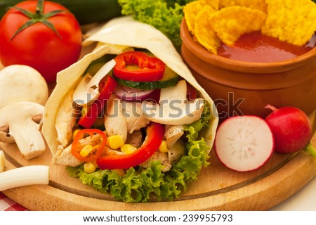Fried spicy chicken and vegetables wrapped in a tortilla roll  - stock photo