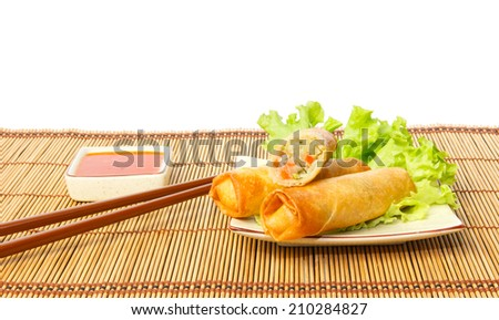 Fried spring rolls on a plate served with chili sauce against white background - stock photo