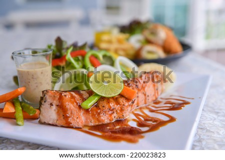 Fried steak from a salmon with a sauce and lemon, ready to the serve - stock photo