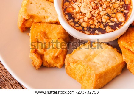 Fried Tofu, Crispy outside and Soft inside. Dip with Sweet and Sour Tamarind Sugar Chilli Sauce, Top with Peanut Crusted. Fresh Homemade Healthy Cooking Idea. Close up. - stock photo