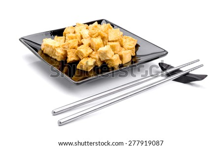 fried tofu, soy products on black plate bowl on white background - stock photo