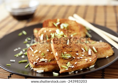 Fried tofu with sesame seeds, chives, and soy sauce - stock photo