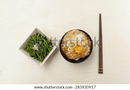 Fried vegetable and rice with crispy fried egg with space on wood table - stock photo