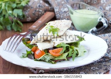 Fried white fish fillet with salad of lettuce, arugula, greens, tomatoes, green sauce with pea, parsley - stock photo
