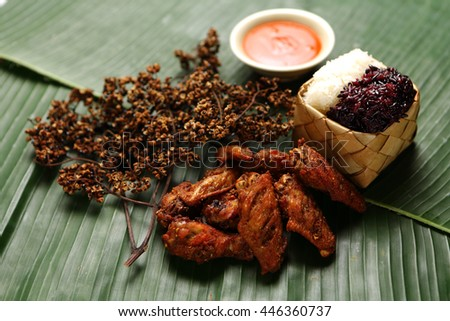 fried wings chicken and sticky rice on banana leaves, spicy herb, Thai food. - stock photo