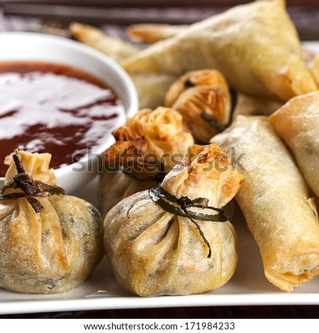 Fried wontons with sweet chili dipping sauce. - stock photo