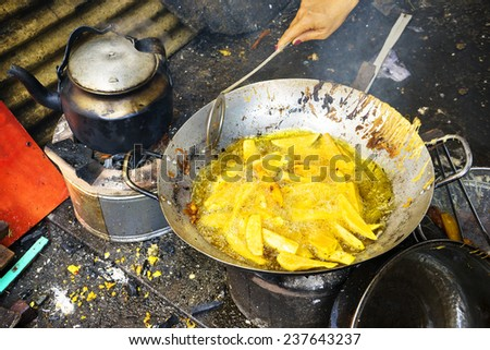 Fried yam in boiling oil in pan, Ho Chi Minh city, Vietnam. It's street food of vietnamese people. - stock photo
