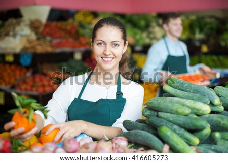 Friendly adult market stuff offering for retail slicing cucumbers - stock photo