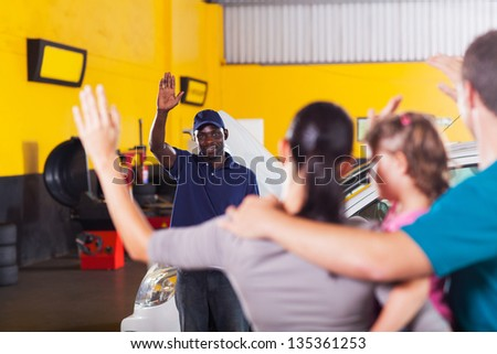 friendly african auto repair shop worker waving good bye to customer - stock photo