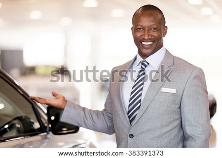 friendly african car dealer presenting new vehicle in showroom - stock photo