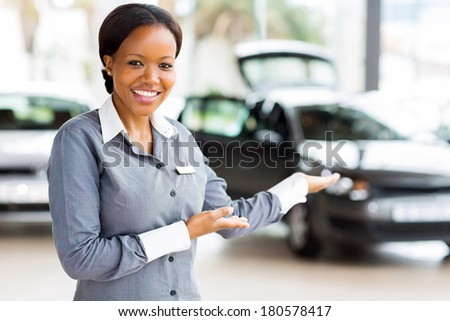 friendly african car saleswoman presenting new vehicles - stock photo