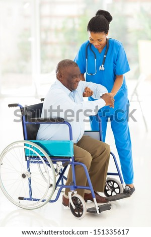 friendly african caregiver helping senior man getting up from wheelchair - stock photo