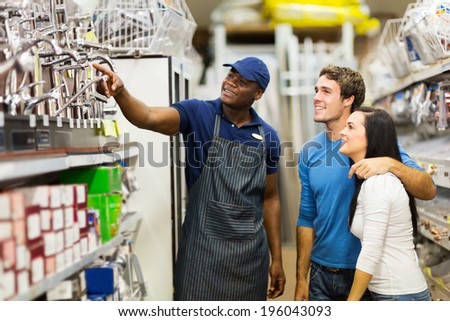 friendly african hardware store assistant helping young couple choosing taps - stock photo