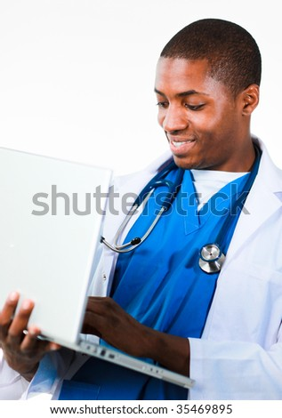 Friendly Afro-American doctor working on a laptop wearing scrubs - stock photo